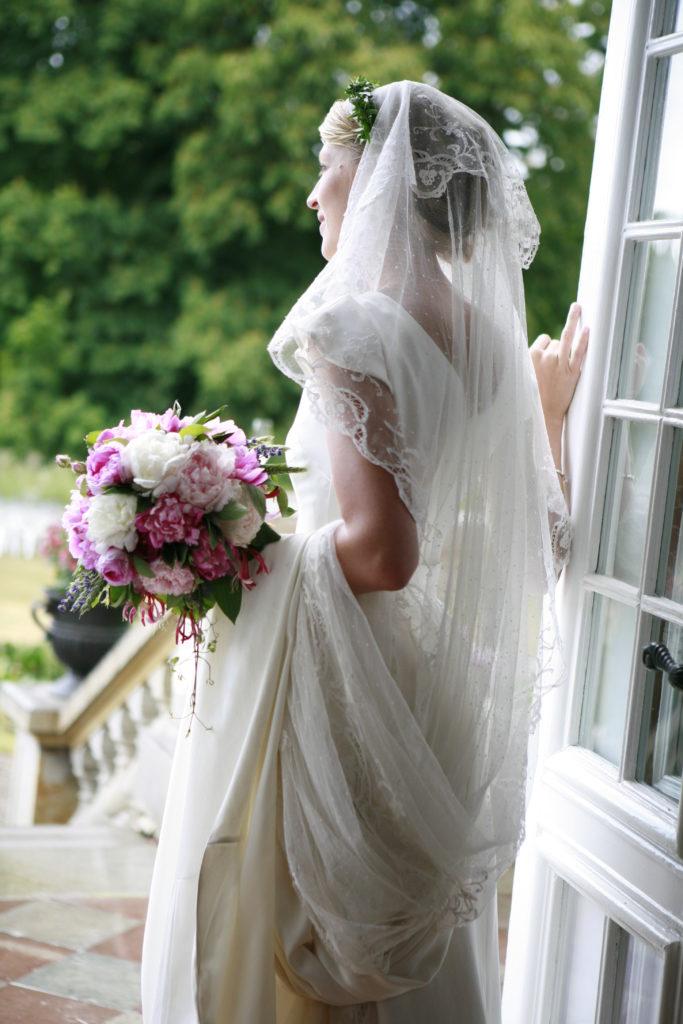 Brud med blommor i dörr