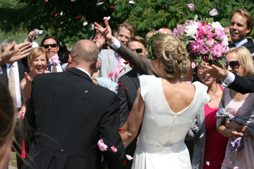 Brudpar som välkomnas av bröllopsgästerna