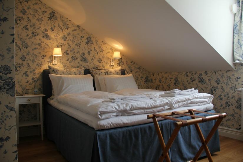 Sovrum med dubbelsäng och två tända lampor