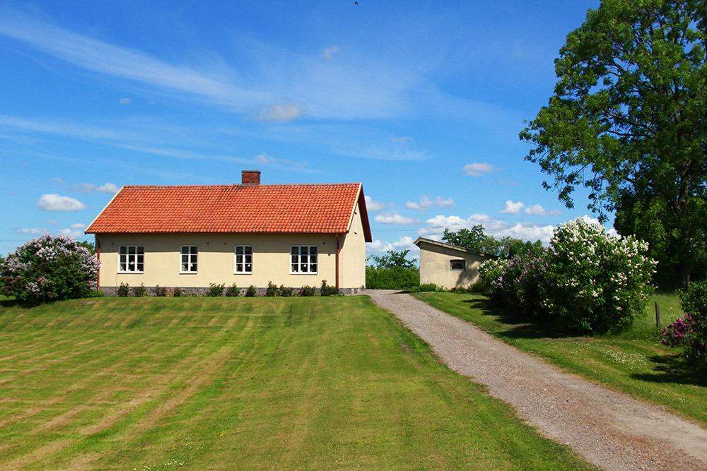 Gult bostadshus med gräsmatta och grusväg