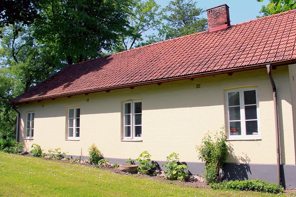 Gult bostadshus med plantering längs väggen