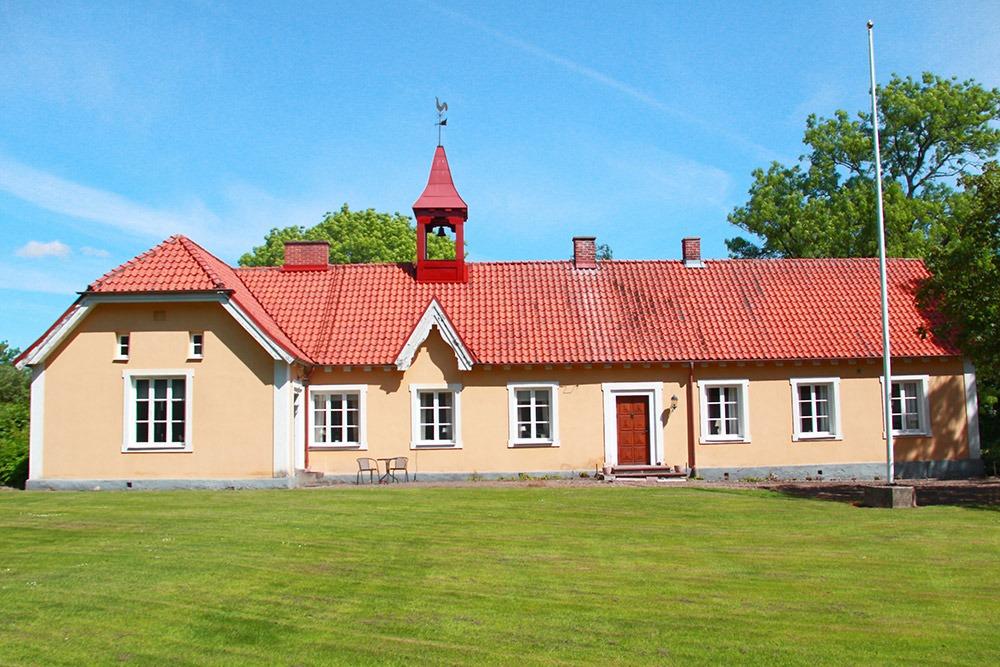Gult bostadshus med rött tegeltak och liten klockpelare på taket.