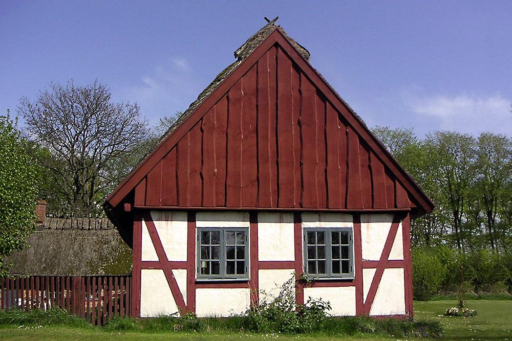 Korsvirkeshus i vit puts och rött trä