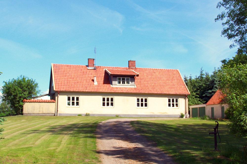 Gult bostadshus med gräsmatta och grusväg framför.